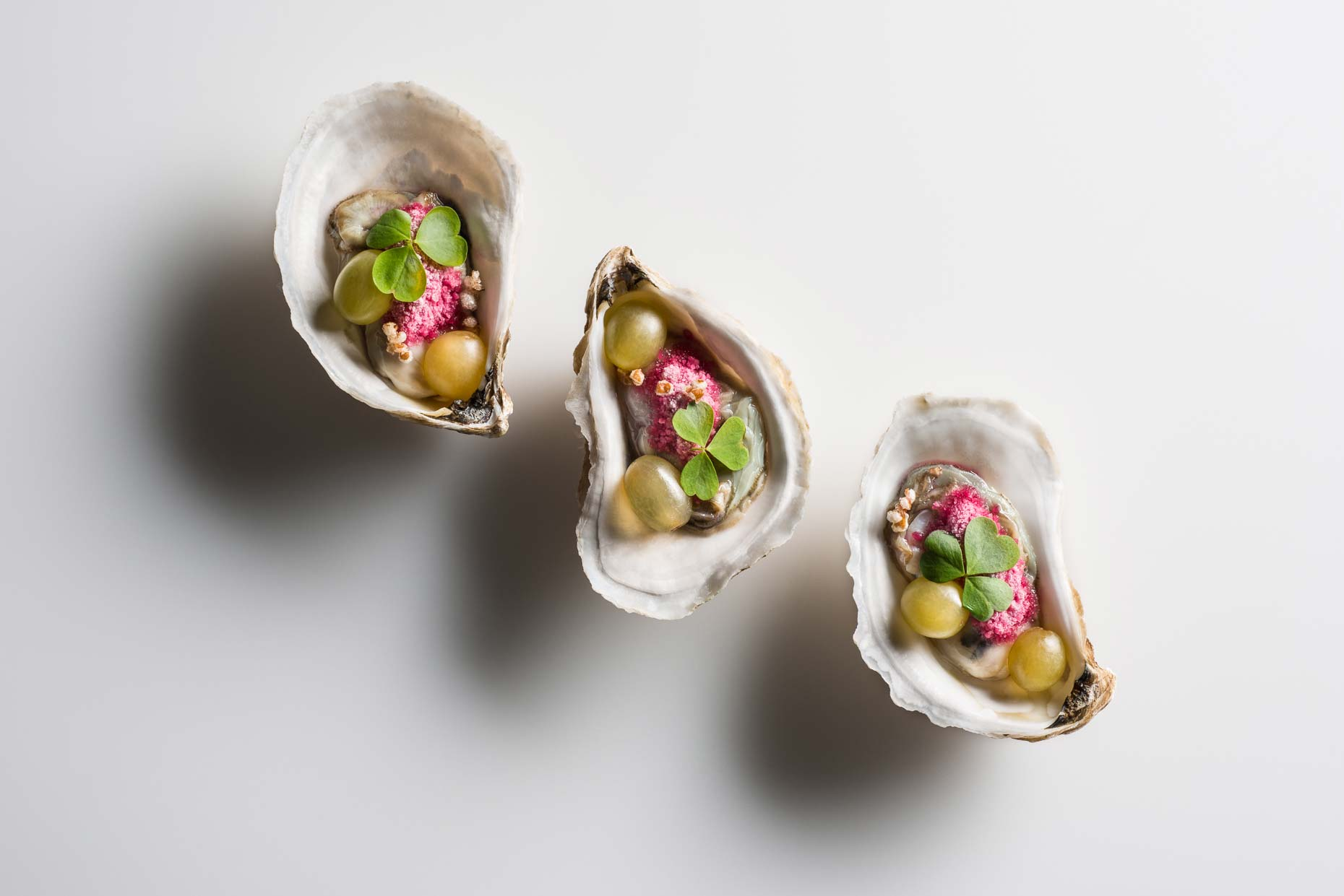 Three Widow's Hole Oyster with baby green grapes topped with lucky sorrel, crispy bulgur wheat, and a dusting of grape mignonette snow on a white background. Prepared by Daniel Humm, Chef/Owner of Eleven Madison Park, NY.